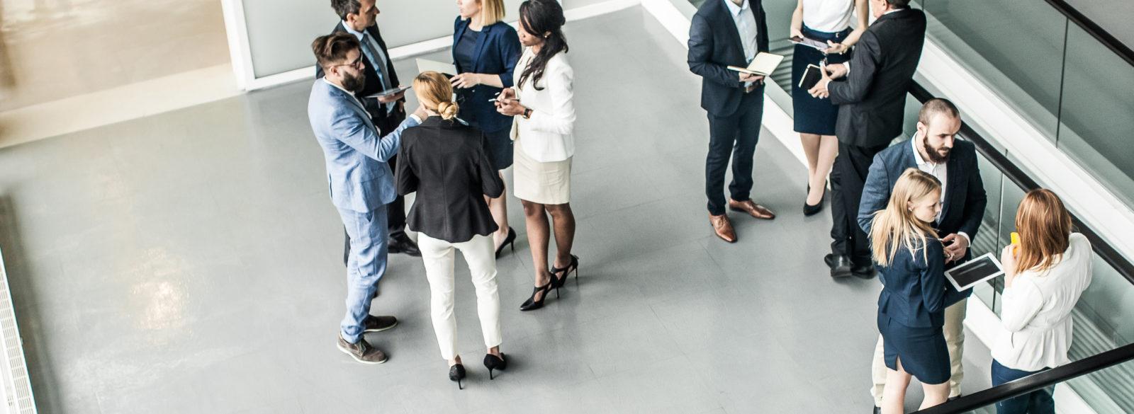Vue en plongée sur un hall bondé de groupes d'hommes et de femmes d'affaires en discussions.